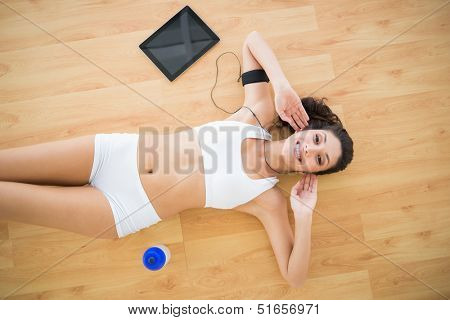 Fit smiling woman doing sit ups at home on parquet floor