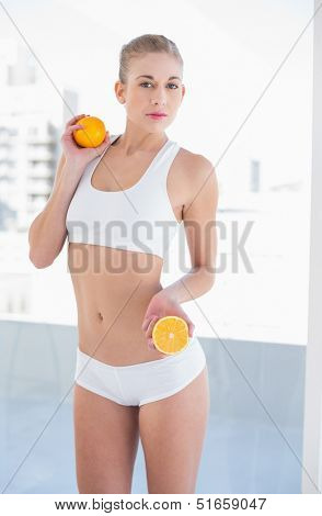Unsmiling young blonde model in white sportswear holding an orange and a half