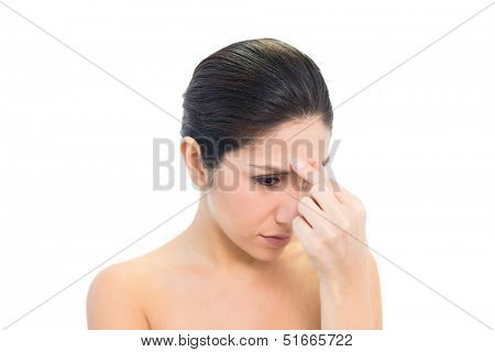 Frowning brunette with a headache pinching her nose on white background