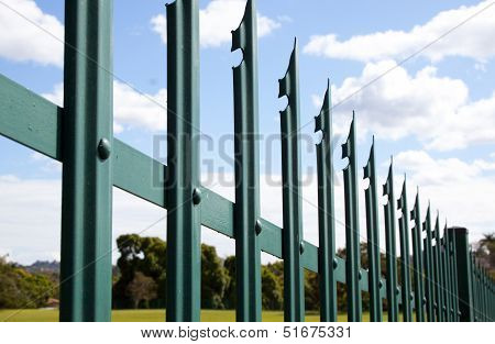 Section Closeup Of Green Palisade Security Fence Against Blue Sky