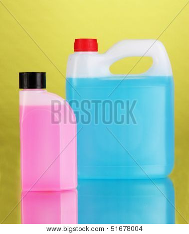 Blue and pink liquids for car in canisters on green background