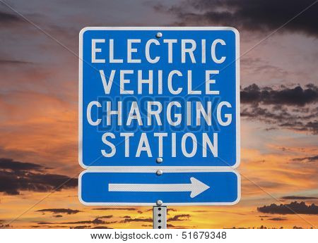 Electric vehicle charging station sign isolated with sunset sky.