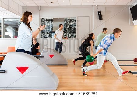 Side view of young friends bowling together in club