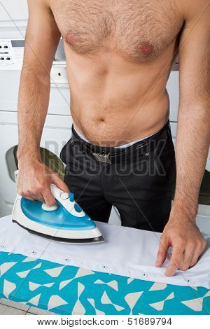 Midsection of shirtless man ironing shirt on table at laundromat