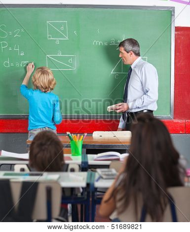Rear view of little boy writing on board while teacher looking at him in classroom