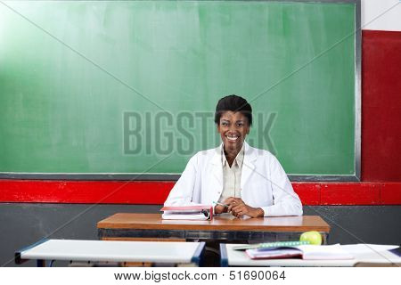 Portrait of happy young African American female teacher sitting at desk in classroom