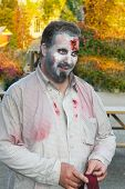 pic of gruesome  - Business man with splatters of blood on him wonders in a park - JPG