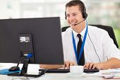 stock photo of helpdesk  - handsome technical support operator working on computer - JPG