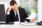 stressed businessman reading documents in office