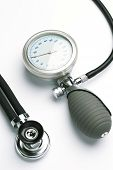 stock photo of sphygmomanometer  - A blood pressure meter or sphygmomanometer and a stethoscope over a white background - JPG