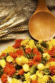 pic of tablespoon  - tricolor Pasta fusilli pile with wooden tablespoon on burlap