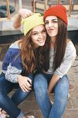 stock photo of friendship day  - Two young happy girl friends sitting together on longboard and having fun - JPG