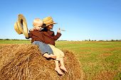 stock photo of hay bale  - Two happy young children a boy and his baby brother are sitting on a hay bale in a field on a farm wearing straw cowboy hats - JPG