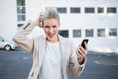 Furious stylish businesswoman holding her phone outdoors on urban background