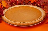 stock photo of pumpkin pie  - Pumpkin pie with autumn leaves decor on orange - JPG