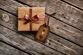 stock photo of paper craft  - Vintage gift box with gift tag with hearts on old wooden background - JPG