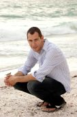 Handsome Male Model Crouching At Beach Looking At Viewer