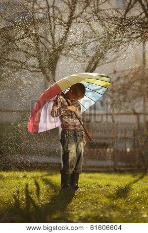 sad boy with colorful rainbow umbrella