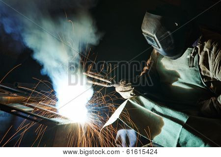 welder working with electrode at arc welding in manufacture production plant