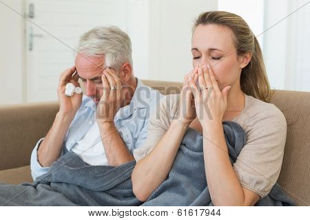 Sick couple sitting on the couch under a blanket at home in the living room