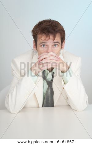 Young Sorrowful Person In White Suit Sits At Table