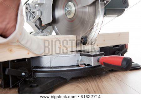 Worker Cutting Timber Using Circular Saw