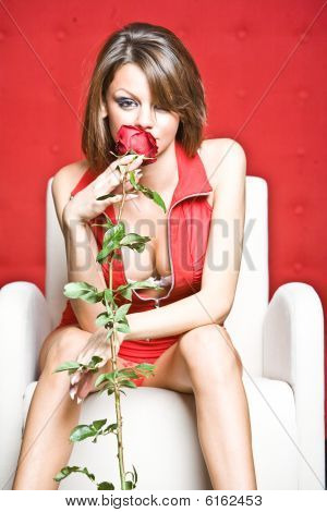 Attractive Woman Smelling Red Rose
