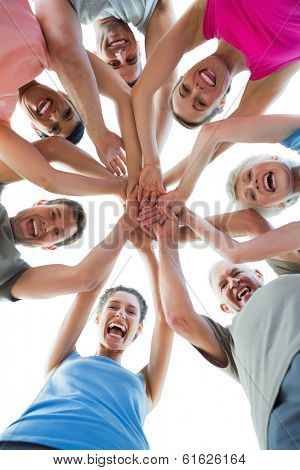 Low angle portrait of happy sporty people holding hands together