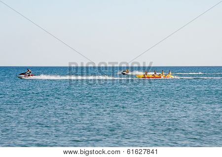 Attraction On The Beach In The Crimea - Jetski Carries Tourists On A Banana