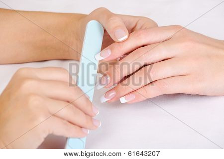 Manicurist doing the  polishing female fingernails with the french manicure