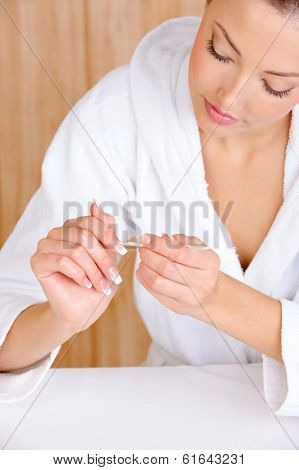 Young beautiful female  removing cuticle from fingers using the cosmetic stick