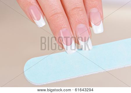 Woman polishing fingernails on hand with nailfile - macro shot, soft focus