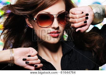 Glamour stylish beautiful  woman with fashion sunglasses and black manicure
