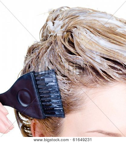 Fragment of woman's head coloring with brush and hair-dye - close-up