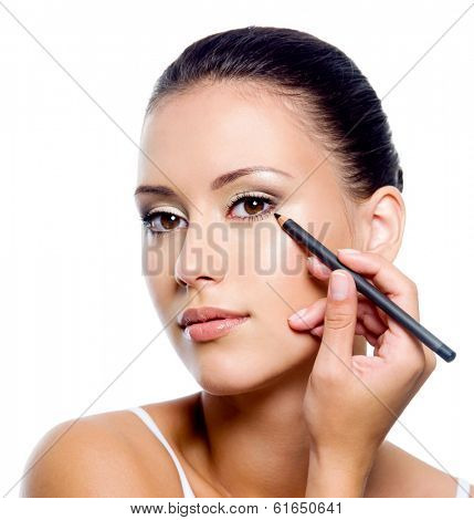 Young beautiful woman applying eyeliner on eyelid with pencil - isolated