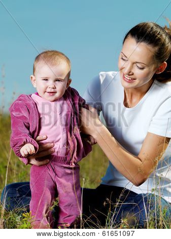 Portrait of happy young beautiful mather with smiling  baby  on nature outdoor