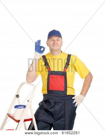Worker on ladder showing sign okey.