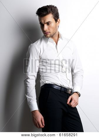 Fashion portrait of young man in white shirt poses over wall with contrast shadows