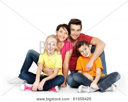 Portrait of the happy  family with two children sitting at studio on white floor