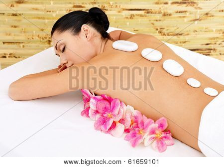 Body care for young woman at beauty spa salon. White hot stones on female back.