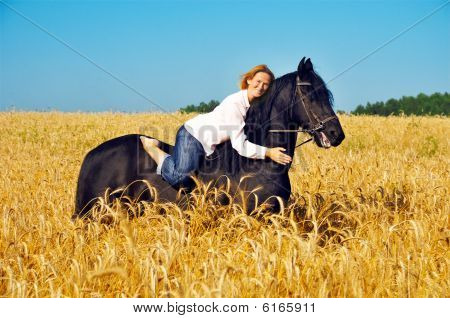 Beautiful Smiling Woman Rides And Pets Horse In Field
