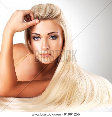 Beautiful woman with long straight blond hair. Fashion model posing at studio.