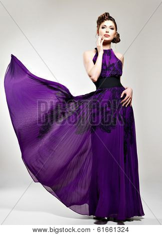 Beautiful fashion woman in purple long dress  hairstyle with pigtails design, poses at studio