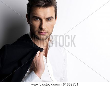 Fashion young man in white shirt holds the black jacket  over wall with contrast shadows