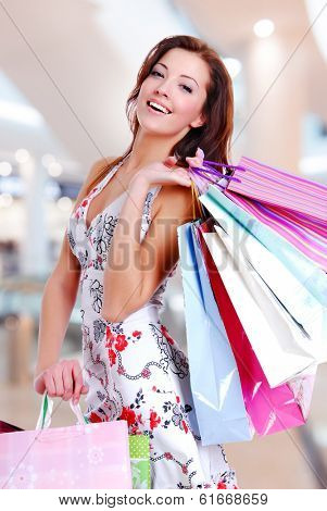 Happy beautiful woman with shopping bags stands at shop