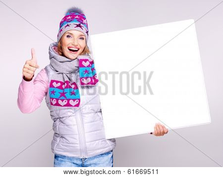 Smiling  woman in winter outerwear holds the banner with thumbs up sign