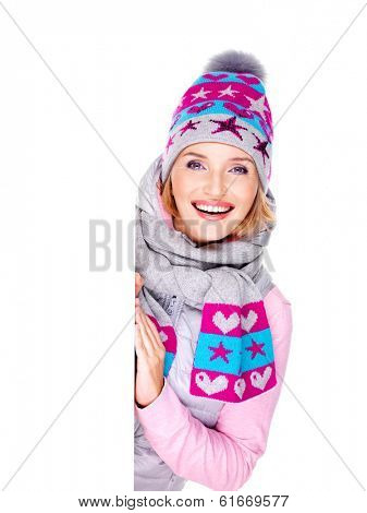 Smiling  woman in winter outerwear holds the white banner in hands at studio