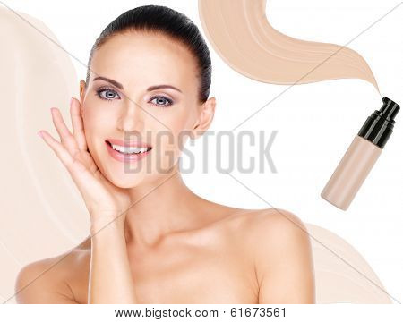 Model face of beautiful smiling woman with foundation on skin make-up cosmetics .