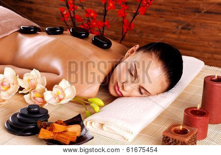 Adult woman relaxing in spa salon with hot stones on back. Beauty treatment therapy
