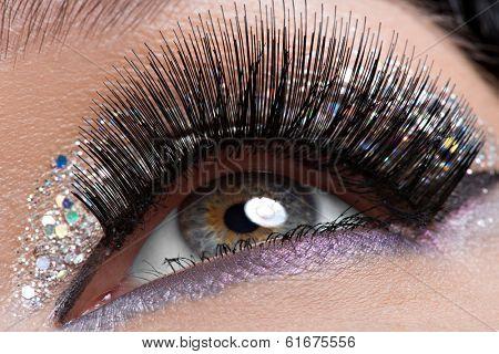 Closeup woman's eye with long black false eyelashes and  creative fashion bright makeup